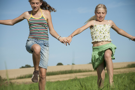 about age: Two carefree happy young girls running meadow