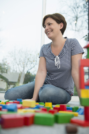 sitting on the ground: Mother with building bricks