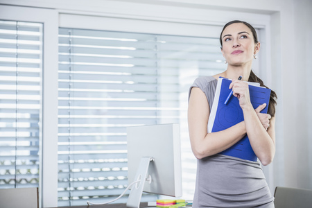 Businesswoman holding files and standing against a table in an office, Munich, Bavaria, Germany