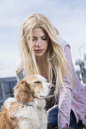 Low angle view of teenage girl looking at her dog, Munich, Bavaria, Germany