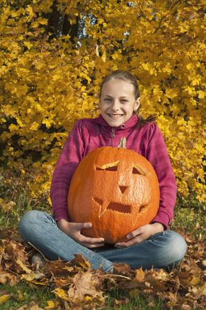 Girl holding halloween lantern, smiling, portrait