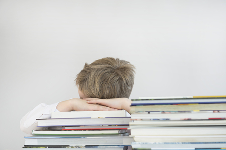 overstress: Boy sleeping on stack of books, close up