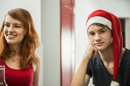public celebratory event: Happy woman with bored young man on Christmas eve, Munich, Bavaria, Germany