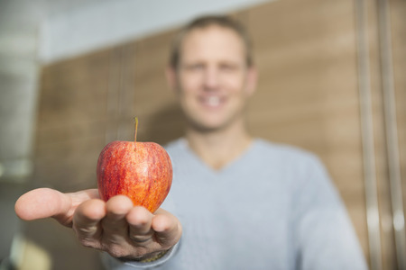Man offering  red apple