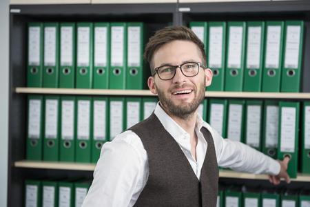 Man young office shelves filing cabinet smiling LANG_EVOIMAGES