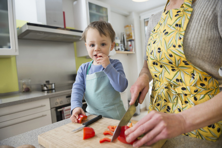 help section: Son nibbling vegetables while mother is cutting them
