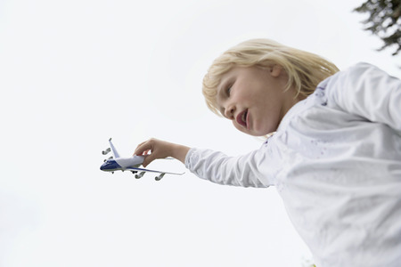 Young blonde girl flying model airplane LANG_EVOIMAGES