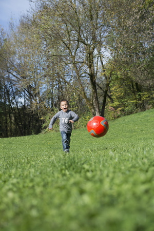 lust for life: Small boy running football meadow playing