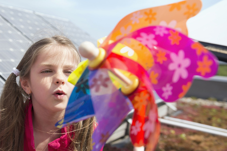 Young girl kid blowing on toy windmill wind