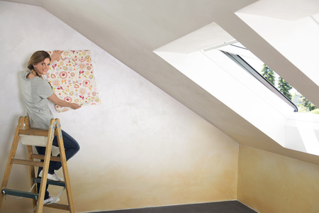 Woman ladder sitting holding wallpaper pattern