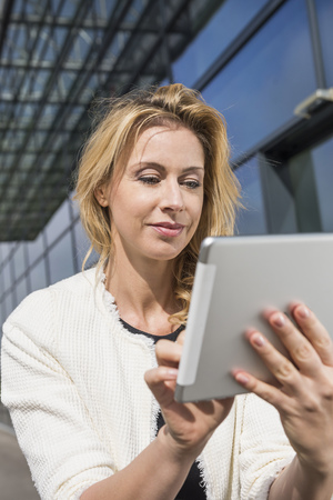 technology: Attractive blond businesswoman tablet computer LANG_EVOIMAGES