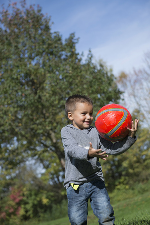 lust for life: Young boy catching red football happy