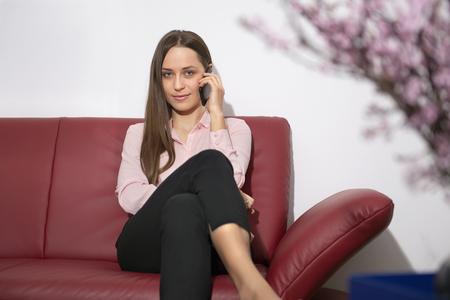 premises: Young woman sitting sofa mobile phone waiting