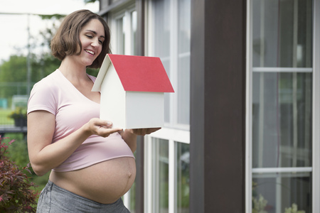 tummy time: Woman holding model house positive future