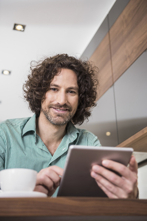 mid morning: Man using a digital tablet in a kitchen, Munich, Bavaria, Germany