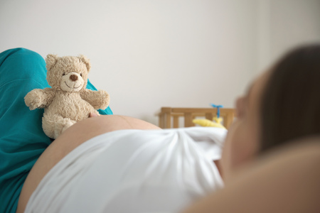Pregnant woman bed lying holding toy teddy bear LANG_EVOIMAGES