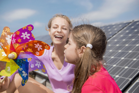 Two girls solar panel toy windmill