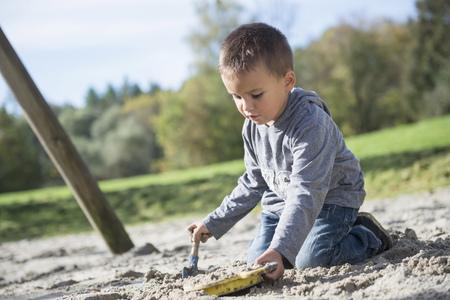 Portrait boy playing shovel sieve sand playground