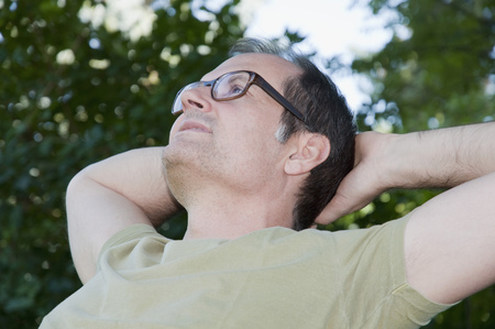 Mature man thinking and relaxing in garden LANG_EVOIMAGES