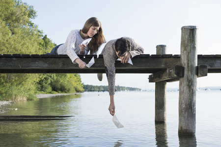 Young man woman launching paper boat jetty LANG_EVOIMAGES