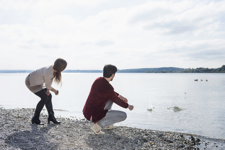 skimming: Young couple lake skimming stones LANG_EVOIMAGES
