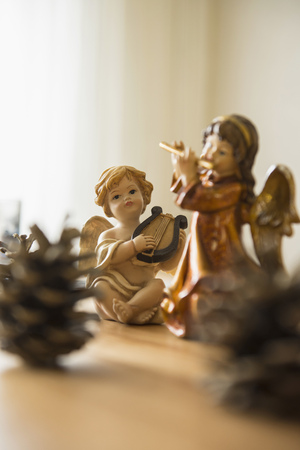 decorative christmas angel figurines with musical instruments and pine cone on the table bavaria