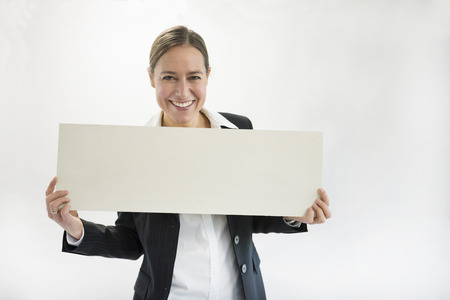 beings: Portrait of businesswoman in black suit holding blank placard, smiling