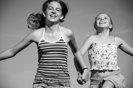 Two young happy carefree girls black and white