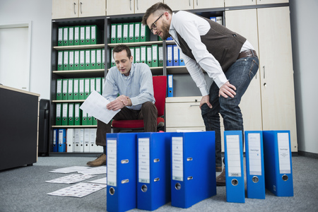 untidy: Men office stress busy sorting filing office LANG_EVOIMAGES