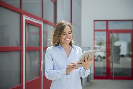 Businesswoman using digital tablet, smiling