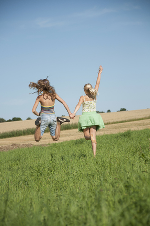 about age: Two carefree happy young girls running field LANG_EVOIMAGES