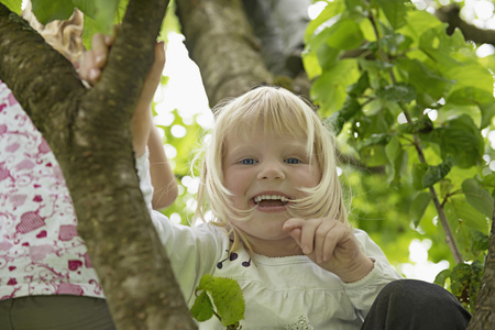 Small blonde girl sitting in cherry tree laughing LANG_EVOIMAGES