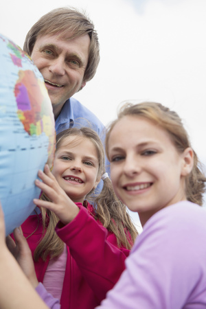 Father daughters holding balloon globe smiling