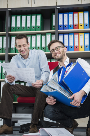 messy clothes: Businessmen busy sorting filing office happy
