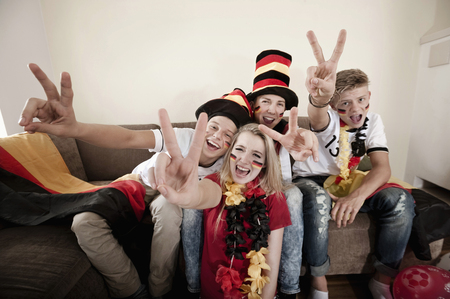 Teenage soccer fans posing in living room