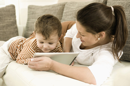 Mother and son using digital tablet in living room, smiling LANG_EVOIMAGES