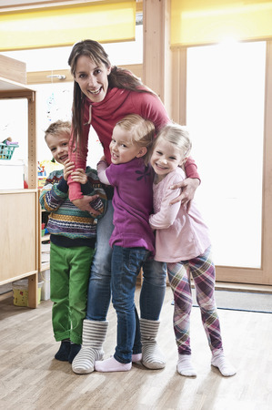 twee: Group picture of female educator and three kids standing in kindergarten LANG_EVOIMAGES