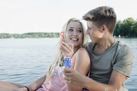 straight path: Teenage couple blowing soap bubbles on a jetty at lake