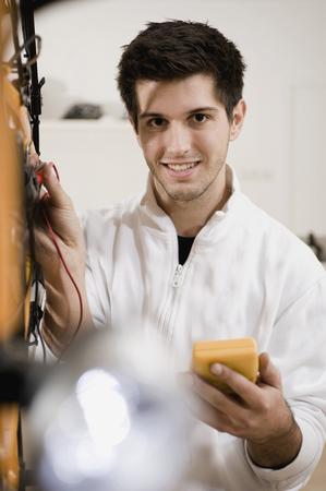 Mechanic testing electric system, smiling, portrait LANG_EVOIMAGES