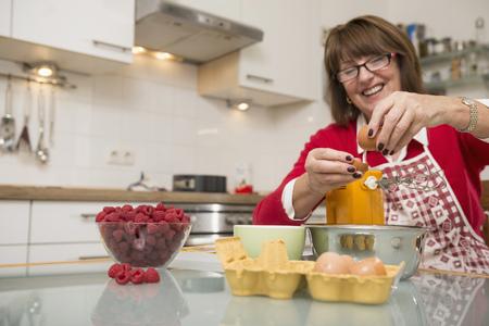 Senior woman dividing egg white and egg yolk in kitchen, Munich, Bavaria, Germany LANG_EVOIMAGES