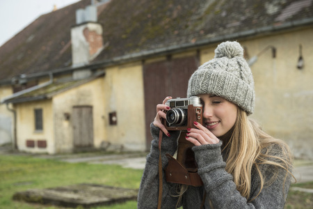Teenage girl clicking pictures with retro styled camera, Munich, Bavaria, Germany LANG_EVOIMAGES