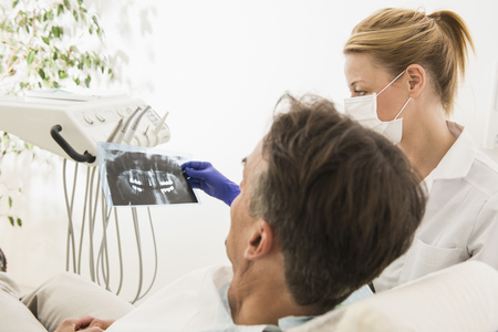 radiogram: Female dentist discussing an X-ray report with patient, Munich, Bavaria, Germany