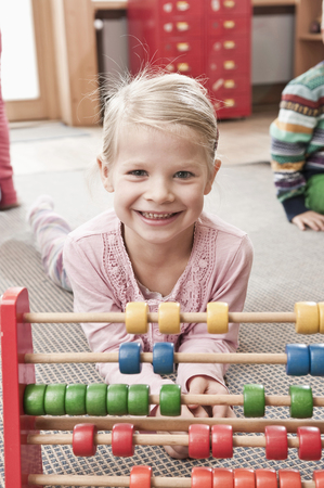 figuring: Portrait of little girl playing with wooden slite rule in her kindergarten