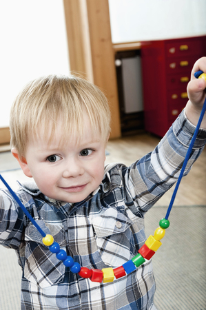 twee: Proud little boy showing selfmade wooden perl necklace LANG_EVOIMAGES