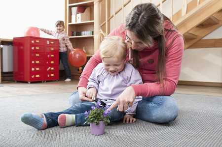 sitting on the ground: Female educator playing with little girl in kindergarten