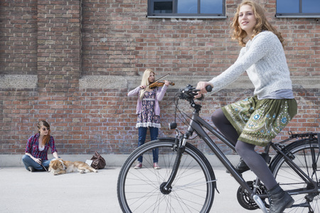 sitting on the ground: Woman riding bicycle on street with teenage girl playing violin in background, Munich, Bavaria, Germany