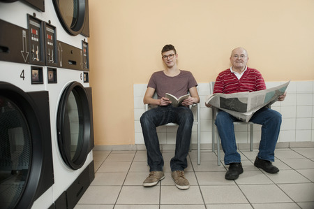 launderette: Men reading book and newspaper in laundry