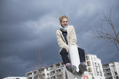 about age: Low angle view of a young woman sitting on wall, Munich, Bavaria, Germany