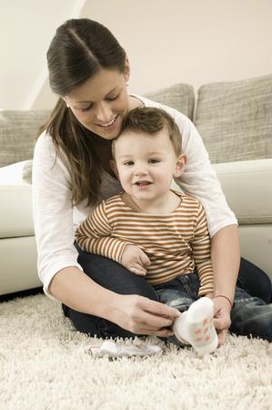 Mother putting socks on son, smiling LANG_EVOIMAGES