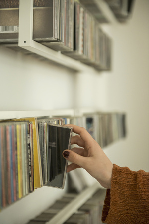 Close-up of a woman hand picking a cd from shelf, Munich, Bavaria, Germany LANG_EVOIMAGES
